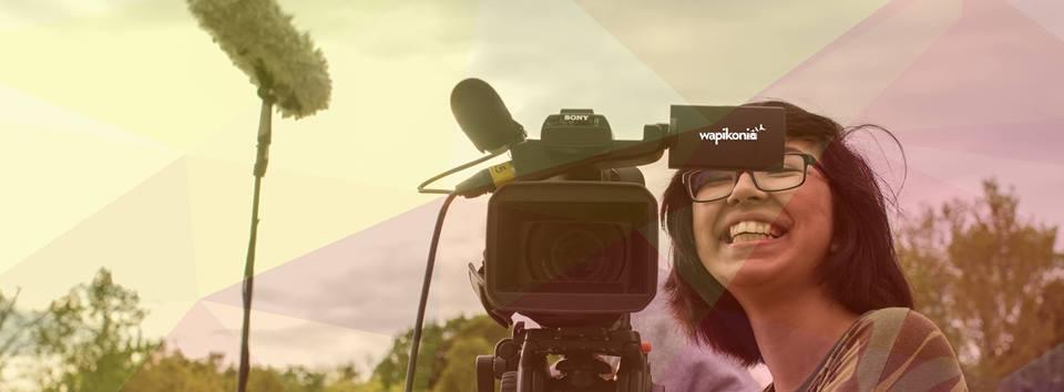 Photo panoramique : une jeune femme très souriante manie une caméra de cinéma.</body></html>