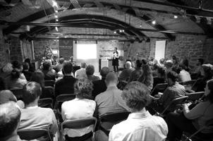Photo en noir et blanc d'une assemblée dans une salle au murs de pierres et au toit vouté.