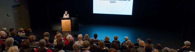 Photo panoramique d'un amphithéâtre où Pascale Mathé donne une conférence avec un écran géant. La salle est comble de gens.