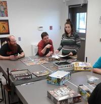 Photo : cinq personnes autour d'une grande table avec plusieurs jeux de plateau. Quatre jeunes adultes et un moins jeune, barbu.