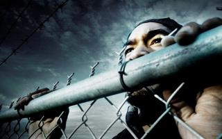 Photo : un homme noir, vu de près, à travers une clôture de métal.</body></html>