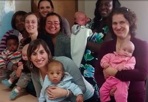 Photo réelle du groupe : sept mères, à diverses couleurs de peau et styles, avec plusieurs bébés.