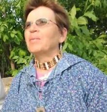 Photo de Marie-Émilie Lacroix, regardant devant à l'horizon. Cheveux courts roux, collier autochtone, chemise mauve-bleu fleurie.