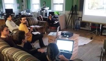 Photo : on voit six personnes dans une grande salle sur des divans, devant un écran blanc sur lequel un schéma est projeté.