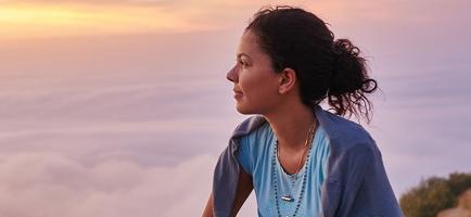 Photo : une dame dans la trentaine est assise sur un sol vert situé au-dessus d'une masse nuageuse blanche. Elle a les cheveux bruns foncés, attachés, et la peau bronzée. Son pendatif ressemble à une balle de fusil.