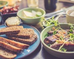 Photo qui accompagne l'annonce : quelques petites « toasts » sur une assiette bleue ; petit plat avec des légumes et tofu grillé ; et autres aliments hors focus.