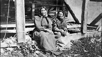 Photo noir/blanc ancienne de deux femmes autochtones assises sur le bord d'une structure en bois carré. Elles portent des robes occidentales d'époque.