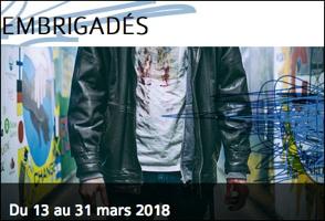 Affichette : sur fond de peinture style graffiti chaotique, on voit seulement le torse d'un jeune homme portant un t-short blanc avec une veste de cuir noir. EMBRIGADÉS du 13 au 31 mars 2018.