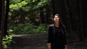 Dans une forêt verte foncée, sur un chemin de terre brune, Natasha Kanapé Fontaine regarde le ciel. Cheveux longs bruns, veste brune foncée et vêtements noirs.
