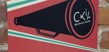 Photo d'une affiche sur un mur de briques rouges intérieures. Un cône noir, soit un porte-voix, et le bout affiche « CKIA 88,3 radio urbaine ». Le fond est rouge, avec deux lignes de couleur vert pâle, en diagonal, en-dessous et au-dessus.