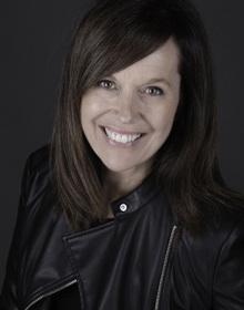 Portrait : souriante, cheveux long bruns, veste de cuir noire à fermeture éclair.
