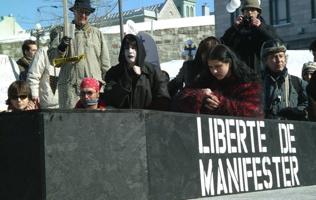 Photo : devant un cercueil noir, sur lequel est écrit « Liberté de manifester ». Une personne, au visage peinturé en blanc, joue la mort. Plusieurs autres autour sont les personnes endeuillées. Un jeune homme a la bouche baillonnée. Un monsieur tient une chandelle.