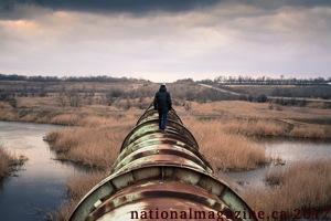 Photo : un homme, de dos, marche sur un gros pipeline d'oré qui passe sur un grand champ marécageux. L'herbe est beige. L'homme n'est pas un travailleur selon son style vestimentaire normal.
