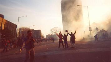 Photo : l'édifice Complexe G est couvert de gaz lacrymogène.  Trois jeunes hommes, les bras levés comme en victoire, devant. Un photographe est aussi dans la photo. Au loin, une foule de gens sur la rue.