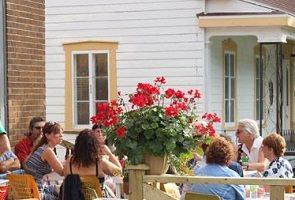 Une dizaine de personnes sur la terrasse au soleil, de style café, sur le devant d'une ancienne église et à côté d'une maison blanche.