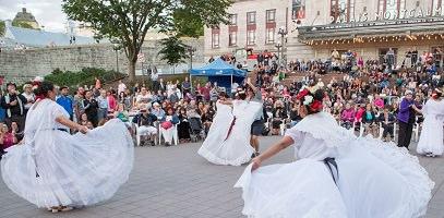 Trois danseuses en grande robe blanche, tenue en quelque sorte en éventail. Une agit plus comme cheffe d'orchestre. Foule  dense et colorée de gens sur les marches devant le Palais Montcalm.