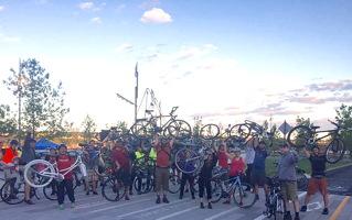 Foule d'environ 30 personnes avec leur vélo. Plusieurs tiennent leur vélo au-dessus de leur tête. Derrière, le mas d'un ancien navire, donc probablement dans un parc historique de Québec.