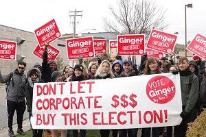 Photo : manif pour la campagne de Gingeré  Plusieurs jeunes, de genres variés, avec des pancartes roses. Bannière se lisant Don't let corporate money buy this election!