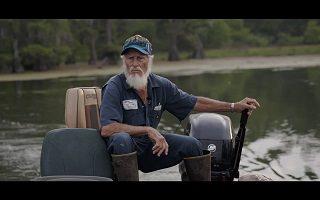 Capture-écran d'une des scène : un homme âgé, l'air sérieux et vénérable, à la barbe blanche et casquette et vêtements bleutée, pilote un petit bateau à moteur sur un lac sauvage.