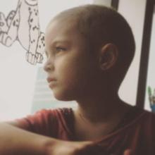 Photo : jeune jolie fille, cheveux rasés, regardant au loin par une fenêtre de la maison.