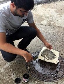 Photo : une personne calque un emblème entouré de lettres grecques, qui est gravé sur une plaque de métal sur le trottoir. Le motif calqué avec l'encre noir sera probablement ensuite transféré sur un vêtement. Le jeune homme est un jeans, t-shirt de Star Wars, lunettes, légère barbe et cheveux noirs.
