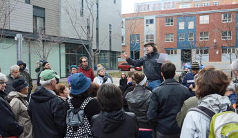 Devant des immeubles d'habitation près de l'Îlôt Fleurie, François G. Couillard parle à une foule d'environ vingt personnes, les mains levés pour exprimer de quoi.</body></html>