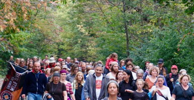 Photo : une centaine de personnes, marchant ensemble, vues de face dans une forêt boréale au soleil. Plusieurs femmes, âges variés. On peut discerner M. Vollant au milieu vers l'avant discutant avec une jeune femme.