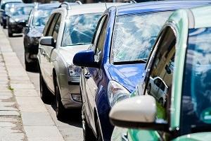 Photo de voitures (teintes bleues) stationnées une derrière l'autre sur le bord d'une rue.
