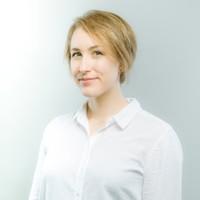 Portrait de Myriam Landry sur fond gris-bleu pâle : cheveux blonds courts, regard souriant, peau blanche, chemise blanche relaxe.
