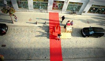 Photo officielle de l'événement : une rue vue du ciel, environ 50 pieds au-dessus de six personnes qui ont installé un espace sur le stationnement (une place) devant un magasin et sur le trottoir. Une voiture noire de chaque côté. Une large ligne rouge traverse la zone installée.