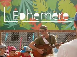 Photo du lieu réel : belle grande bannière « L'Éphémère » sur fond de feuilles verte et orange. Un chanteur avec guitarre, lunettes, souriant, regardant trois jeunes garçons bras-dessus-bras-dessous, joviaux.