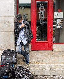 Photo : sur le bord d'une porte rouge à Québec, un homme se tient à côté d'une pile personnel, c'est-à-dire sac-à-dos, sac de poubelle, sac de couchage. Il regarde le sol, fumant une cigarette.