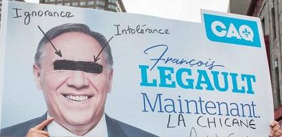 Affiche tenue bien haut qui est en fait une affiche électorale de François Legault mais modifiée avec les mots Ignorance, Intolérance, La chicane.