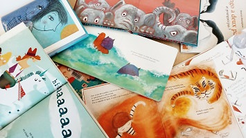 Une dizaine de livres pour enfants, aux couvertures colorées, entassés un sur l'autre.