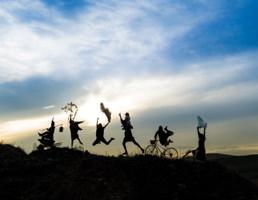Photo : à l'horizon, sous un ciel à la fois lumineux et nuageux, ombres de cinq femmes et hommes dansant, sautant, etc.