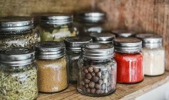 Photo : onze petits pots de verre, avec couvercles en aluminium, remplis de fèves ou d'épices.