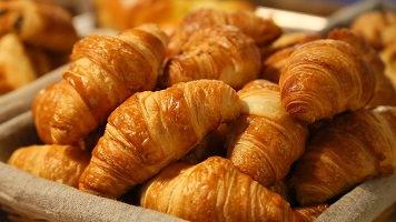 Photo de plusieurs petits croissants (pain) empilés dans un panier.
