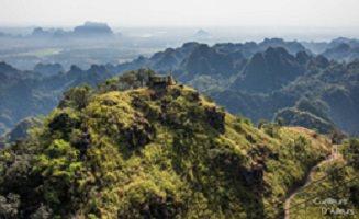 Photo : petite montagne couverte de verdure, plus haute que les autres similaires et nombreuses autour. Il semble y avoir une maison sur le dessus, difficile à voir. On voit très loin et l'image se termine dans une brume lointaine.