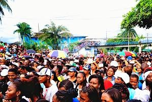 Photo d'une foule rassemblée, climat et végétation de type tropical. Les gens ont la peau foncée, brune. Femmes et hommes.
