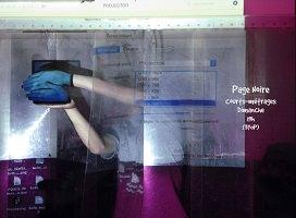 Affichette sur fond d'une photo : une femme peint sur une fenêtre, à partir de l'intérieur, mais la fenêtre inclut le reflet d'un ordinateur! La couleur principale est le mauve, mais ses mains sont couvertes de bleu (peut-être des gants).