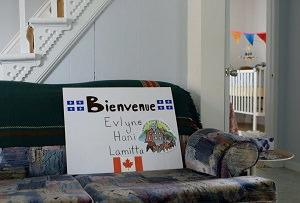 Photo : sur un divan vert, dans une maison aux murs blancs, une affiche blanche Bienvenue Evlyne, Hani et Lamitta. Drapeaux du Québec haut et un du Canada au bas.
