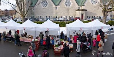 Photo de 2017 : journée ensoleillée d'hiver ; côté de la grande église ; nombreuses tentes pavillons blanches ; des gens visitent divers kiosques.