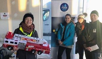 Photo : jeune femme souriante, traits asiatiques, vêtue pour l'hiver, tenant un gros camion de pompiers ; trois autres personnes souriantes sur le côté, deux femmes, un homme.</body></html>