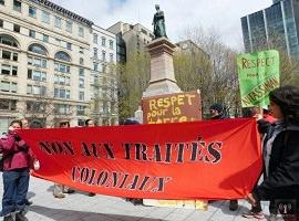 Photo d'un rassemblement devant un monument à Montréal : deux femmes tiennent une bannière rouge se lisant « Non aux traités coloniaux ».