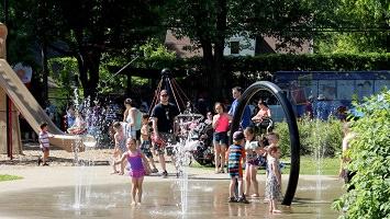 Photo de 2017 : jeux d'eau, enfants dedans, parents autour, glissade, verdure.