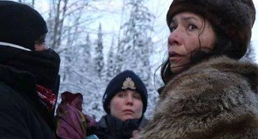 Photo : une femme autochtone, vue de côté, semble inquiète. Elle porte un manteau de fourrure. Devant elle, une femme policière semble calme mais attentive.</body></html>