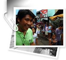 Photo : un jeune homme souriant, peau et cheveux foncés bruns, gilet vert vif, marchant sur une rue achalandée qui semble être en Inde. Une trombone tient la photo.