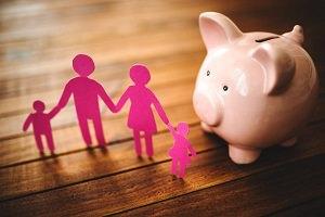 Photo : banque en forme de petit cochon rose sur une table en bois brun. Devant se tient la forme d'une petite famille humaine, découpée de papier rose.