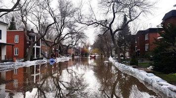 Photo : rue innondée d'eau, aussi bordée de neige, entre des blocs appartement.