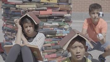 Photo : trois enfants, deux garçons et une fille, au bord d'une tour de livres !  Il fait très soleil et ils utilisent même les livres pour se protéger du soleil.